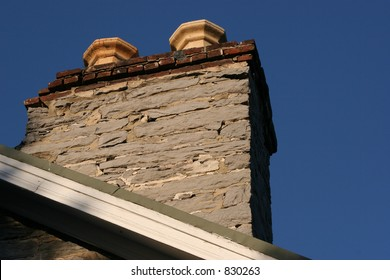 Old stone chimney against blue sky.