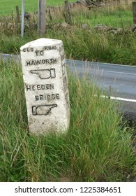 an old stone direction marker on the old road between howarth and hebden bridge with carved fingers indicating the way