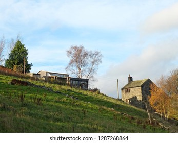 An old stone farmhouse and sheds at the top of a green hillside meadow with trees and stone walls in west yorkshire calderdale countryside