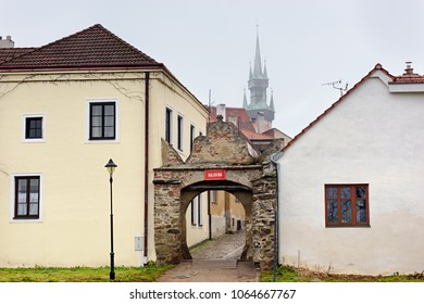 Old stone gate in the historical town. On the gate hangs a sign with the name of the street, written in czech: Tkalcovska street.  Znojmo, Czech Republic, Moravia, Europe