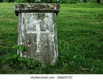 An old stone grave or monument with cross.