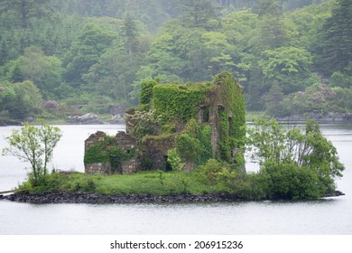 Old stone house, overgrown with plants, on a tiny island in a lake in Connemara, Ireland, on a foggy day.