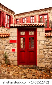 Old stone house with red wooden shutters and red door. Boxes with red and white flowers on the window. Balikesir, Turkey