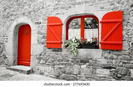 Old stone house with red wooden shutters and red door. Boxes with red and white flowers on the window. Brittany, France. Retro aged photo.