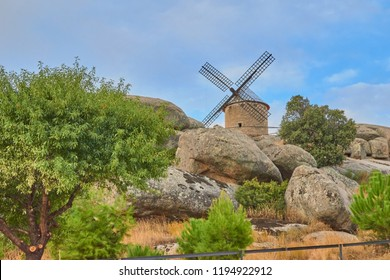 Old stone mill in the background surrounded by trees and vegetation and rocks with blue sky in Las Ventas con Peña Aguilera, Toledo, Spain