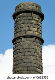 old stone mill chimney in yorkshire with blue sky and clouds