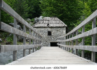 Old stone mill in Valbona, Tropoja, Albania. Grey wooden bridge over the river on the way to the mill
