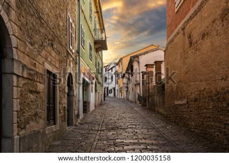 Old stone paved street in town of Motovun in Istria in late afternoon with a series of colored houses and warm cloudy sky