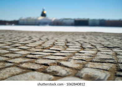 Old stone pavement, creating a soft background of frozen river, blue sky, houses and an Orthodox church with a golden dome. Russia, Saint-Petersburg.