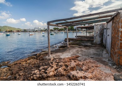 Old stone pier and fisherman house in bay and beach of Sant Antoni de Portmany, Ibiza Island, Balearic islands. Spain.