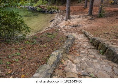 Old stone and rock stairway set in cement descending downhill to the beach area at the lake surrounded by the woodlands on a sunny day in early fall