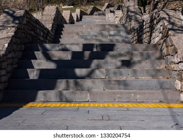 Old stone stairs and yellow tactile paving floor for blind people