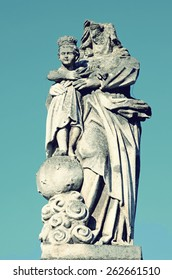 Old stone statue of Jesus and Our Lady of partially destroyed head on the headstone in the cemetery in Ukraine in vintage style