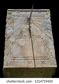 Old stone sundial close up with roman numeral isolated on black background with clipping paths