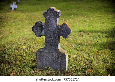 Old, stone, tombstone cross on a background of green grass.