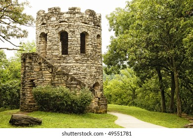 Old stone tower in tranquil setting among lush green scenery (historic landmark, Clark Tower, in Winterset, Iowa).