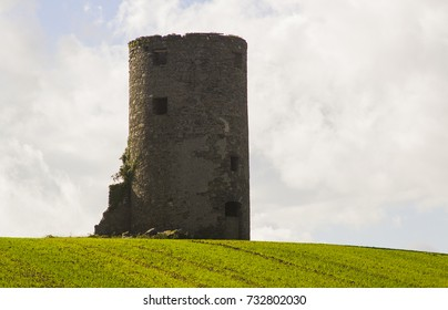 An old stone tower of unknown origin to the photographer on a hill top in a cut hay field on a farm near Kircubbin on the Ards Peninsula in Count down Northern Ireland