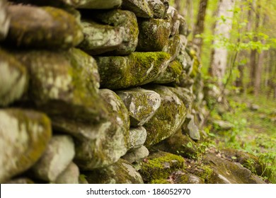 An old stone wall in a forest, covered with moss.  Great Smoky Mountains National Park, TN, USA.