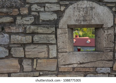 An old stone wall with a loophole in which there is a plastic glass with a brown beverage