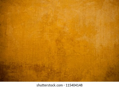Old stone wall painted in yellow,background