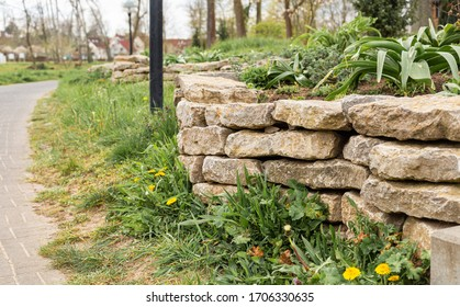 Old stone wall. Park in the city. Small architecture. Stacked stones. Stone pile. Municipal greenery. Lawn with flowers. Daisies and dairy,