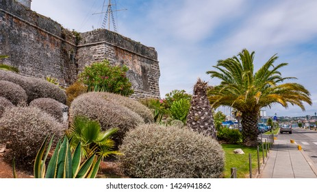 Old stone walls of the Citadel of Cascais, Portugal with beautiful gardens, taken on a cloudy summer day