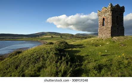An old stone Watch tower over looking Dingle Bay Co. Kerry Ireland as a fishing boat heads out to sea