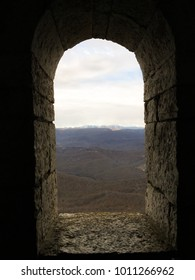 old stone window in the form of an arch with a view of the mountains