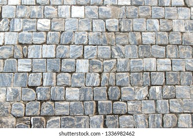 An old stoneblock pavement cobbled with square granite blocks