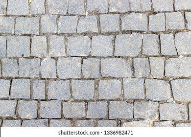 An old stoneblock pavement cobbled with square stone blocks