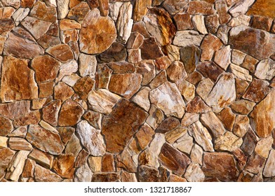 Old stonewall with jagged rocks of different shapes and sizes.