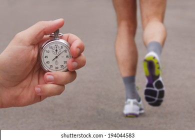 Old stopwatch in a hand and blurred runner athlete feet running on a road