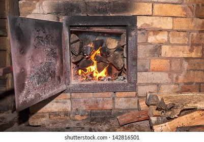 Old stove with open door and burning the wood