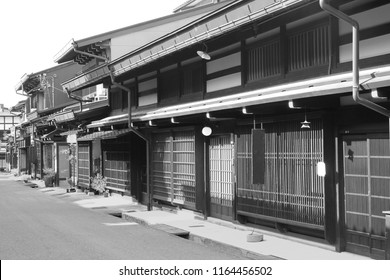 Old street with beautiful preserved traditional wooden houses from Edo period in historic Sannomachi street, Takayama,  Gifu prefecture, Japan. Black and white photo