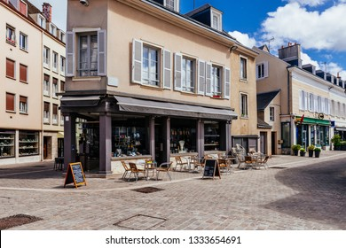 Old street with old houses and tables of cafe in a small town Chartres, France