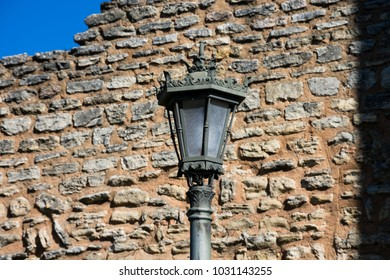 Old Street lamp with a stone brick wall in the background. Ronda, Spain