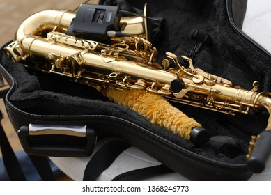 An old street musician's golden saxophone is lying in an open black coffer with a saxophone brush.