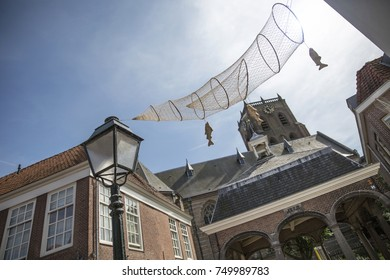 A old street in the Netherlands with a historic architecture and a church in the background. Fishnets hanging in the street.