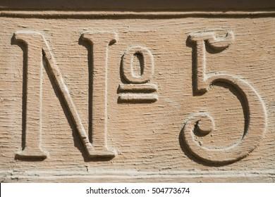 Old street number carved in wood