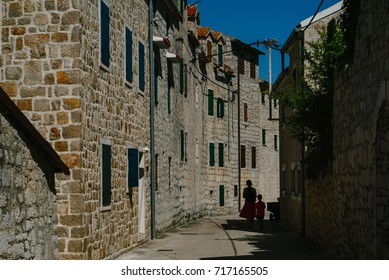 Old street in Prvic Luka with people in shadow
