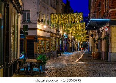 Old street with tables of cafe in center of Brussels, Belgium. Night cityscape of Brussels (Bruxelles). Architecture and landmarks of Brussels.