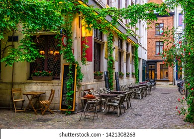 Old street with tables of restaurant in Antwerpen (Antwerp), Belgium. Cozy cityscape in Antwerp