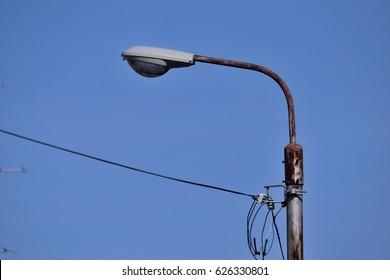 Old streetlight pole against the blue sky.
