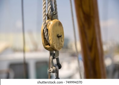 Old and stressed wooden pulley attached to a rope on a sailboat