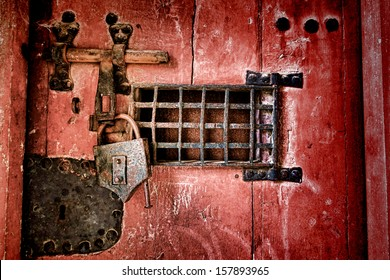 Old strong lock and cast iron latch locking hardware with speakeasy window on a medieval dungeon antique wood jail door