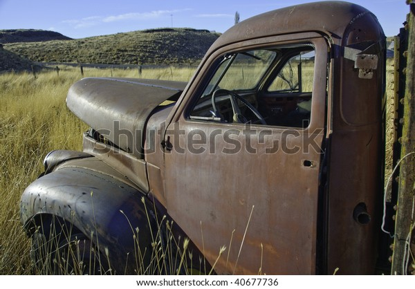 Old studebaker truck rusting in the farm field.It has the morning sun on it.
