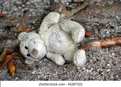 old stuffed teddy bear laying on ground