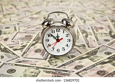 old style alarm clock and on dollars background