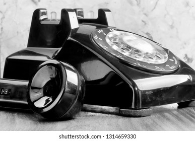 Old style black rotary telephone in black and white.