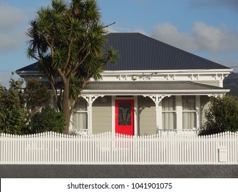 Old style colonial house with red door and picket fence, Petone, New Zealand